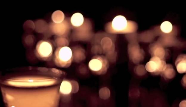 Defocused Candles Behind A Single Softly Glowing Light